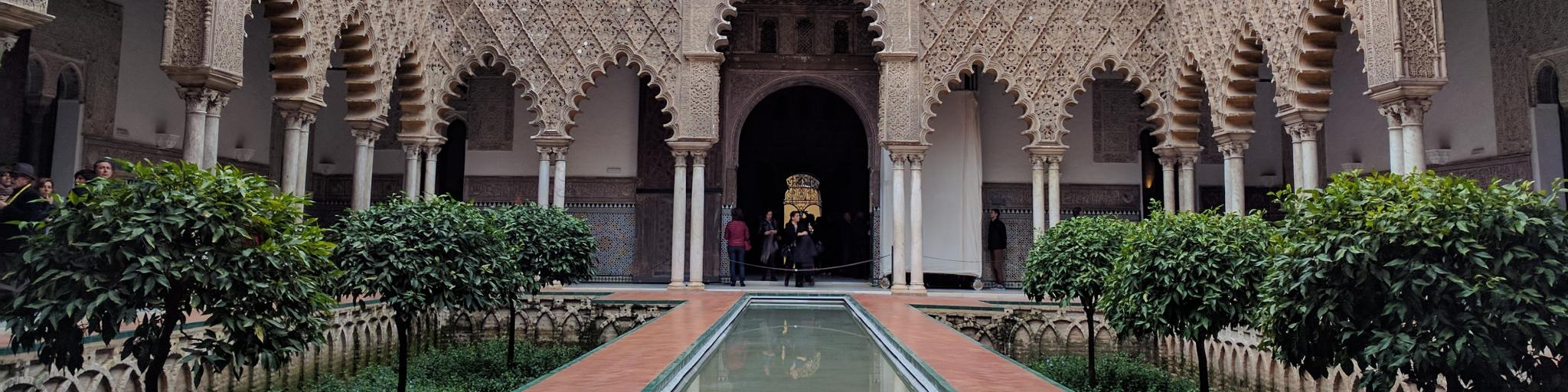 Islamic architecture surrounds a central courtyard in Seville's Real Alcazar