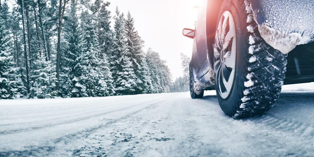 A close up of a car's tyres on a snowy road