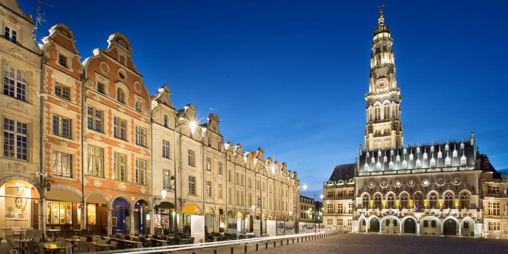 A row of townhouses with curved roofs on Place des Heros, Arras, at night, with the rebuilt belfry in the background.
