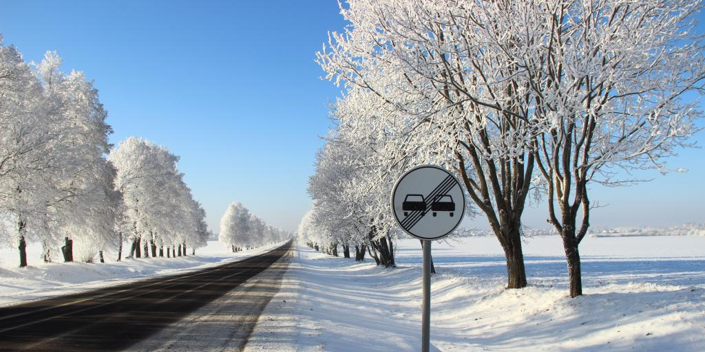 An overtaking prohibited roadsign on the side of an empty main road, with blue sky and snow on the ground and in the trees