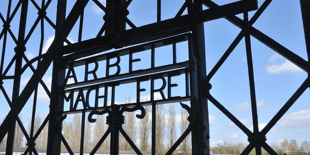 Close up of the words Arbeit Macht Frei on the gates of Dachau Concentration Camp, Munich, Germany, with blue sky visible beyond them