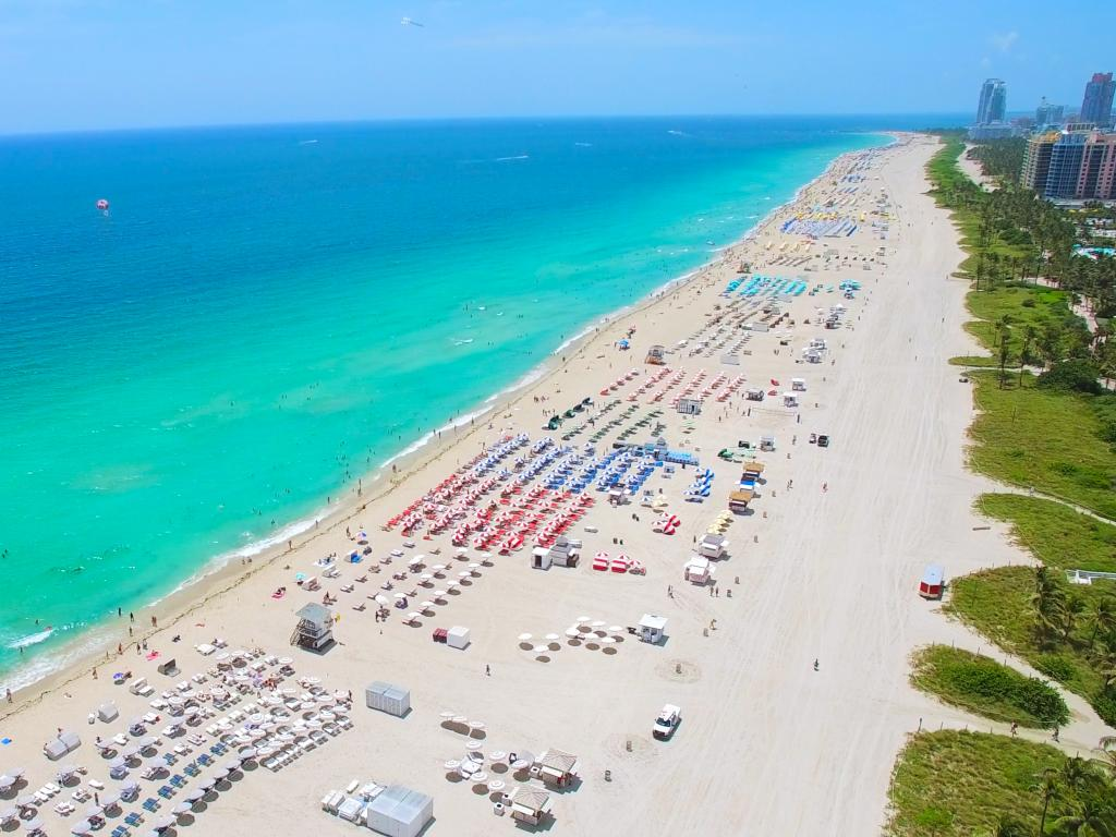 South beach in Miami stretching into the distance with sun loungers everywhere and crystal clear waters.