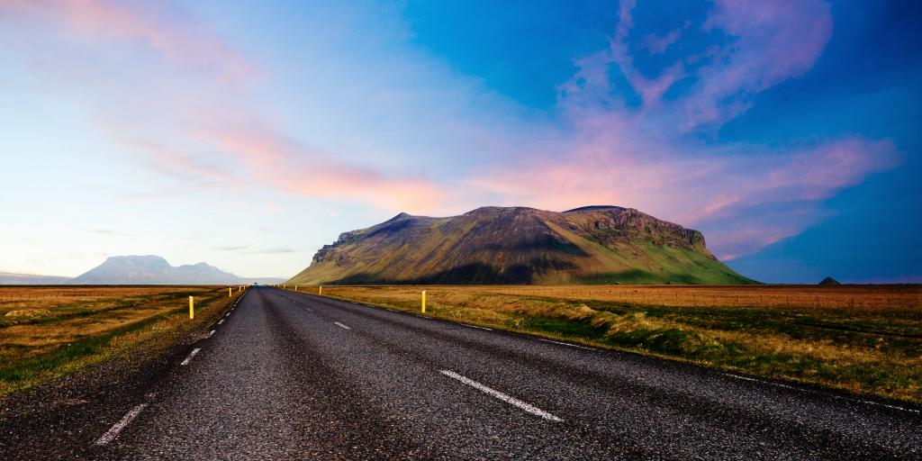 Looking down a road with a mountain to one side during a colourful sunset, in Iceland