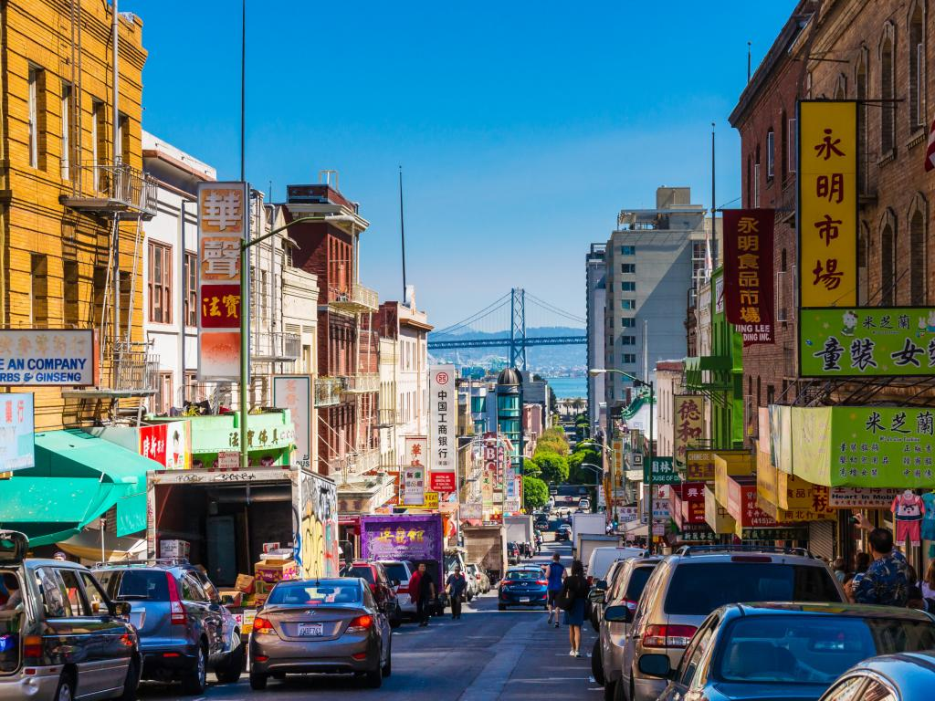A street in Chinatown in San Francisco with the Oakland Bay Bridge in the background