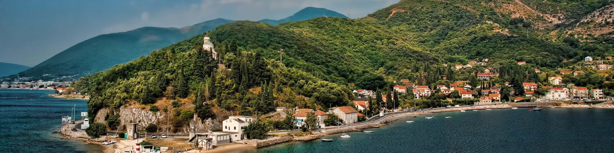 Lush green forests and turquoise water along the coastline of Montenegro