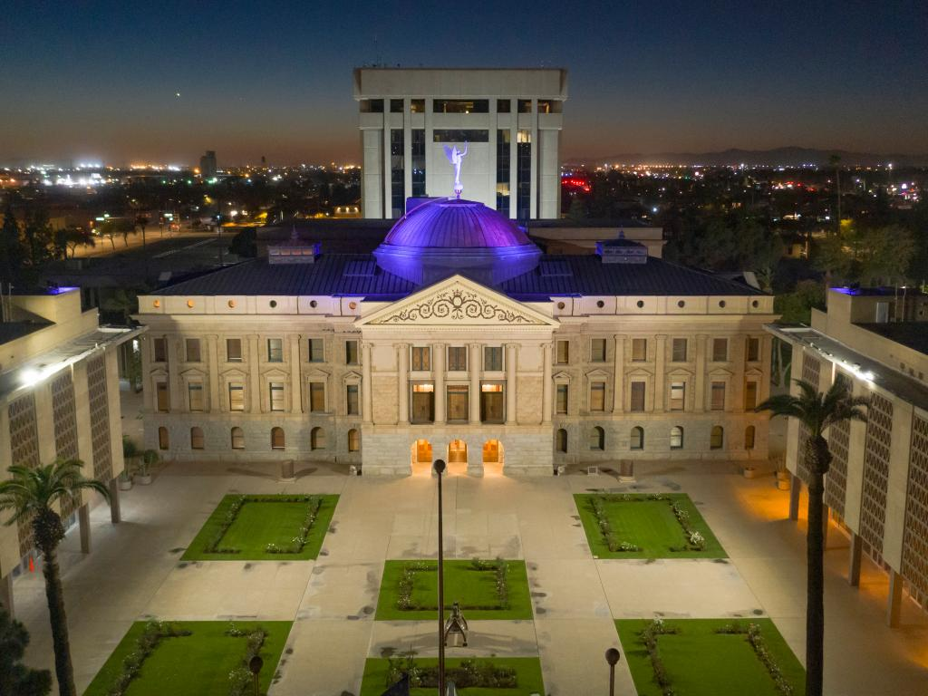 An aerial view of Arizona's Capital building with blue light illuminating its roof and the mesmerizing city lights of Arizona at the back