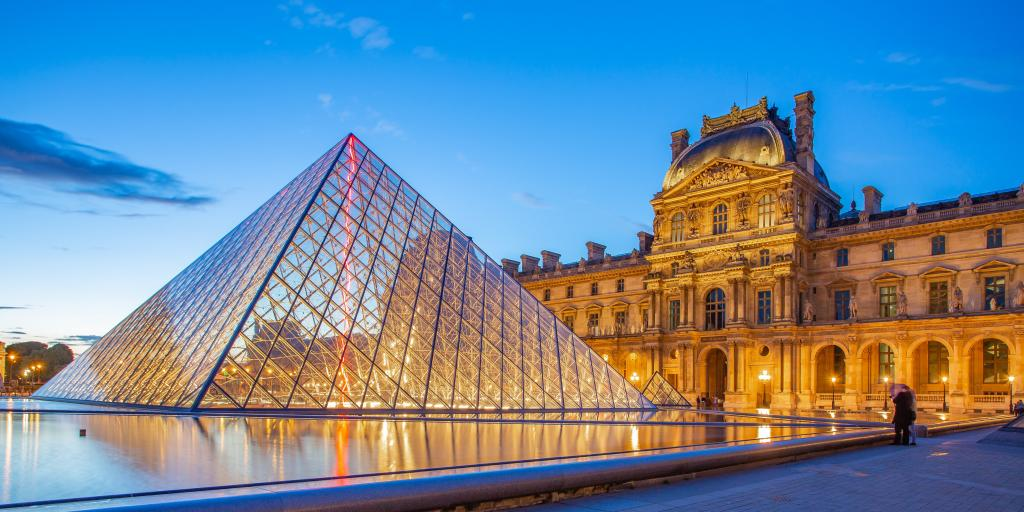The glass pyramid of The Louvre museum, Paris, with its intricate old buildings in the background, at sunset