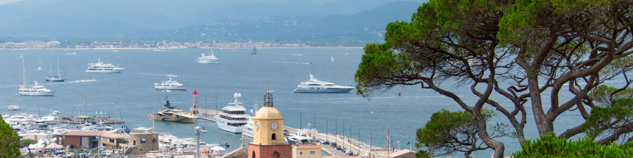 A view of St Tropez, France, from a vista point, with the sea and mountains in the background