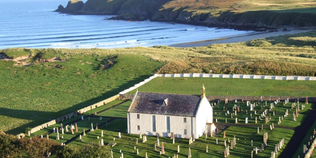 An aerial view of the white exterior of the Strathnaver Museum, Scotland, with a graveyard surrounding it, and a sandy cove and sea in the background