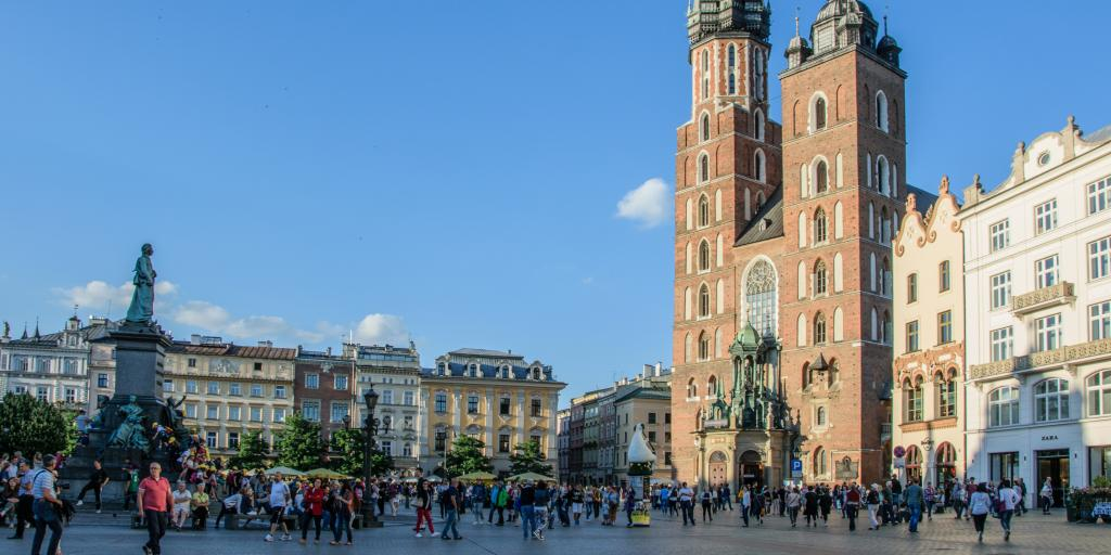 The old market town square in Krakow with people milling around the plaza