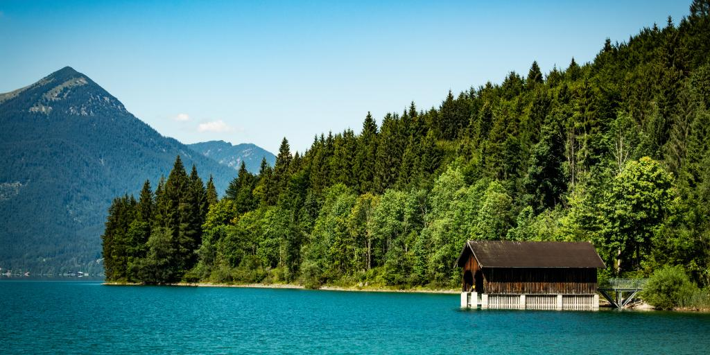 A little alpine hut on a jetty above very blue water in Walchensee Lake, Bavaria, Germany, with pine trees and mountains in the background