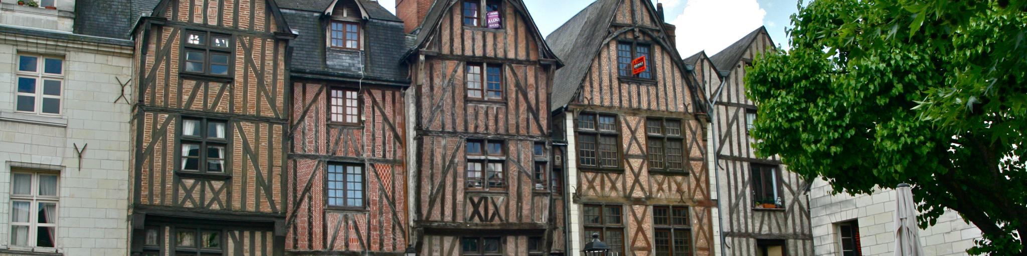 Half-timbered houses line a square in Tours, France, where people sit on cafe terraces eating and chatting
