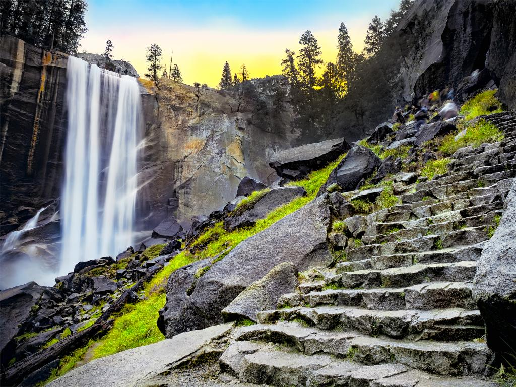 The image shows the Vernal Falls on the left and its staircase trail on the right side at dawn.