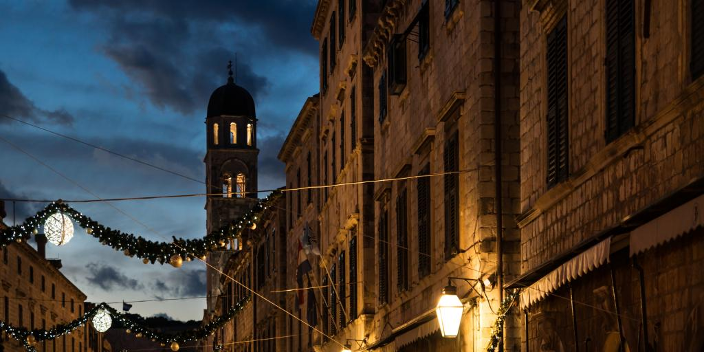 Stradun old street with bell tower decorated with shining Christmas lights and ornaments at dawn, Dubrovnik, Croatia