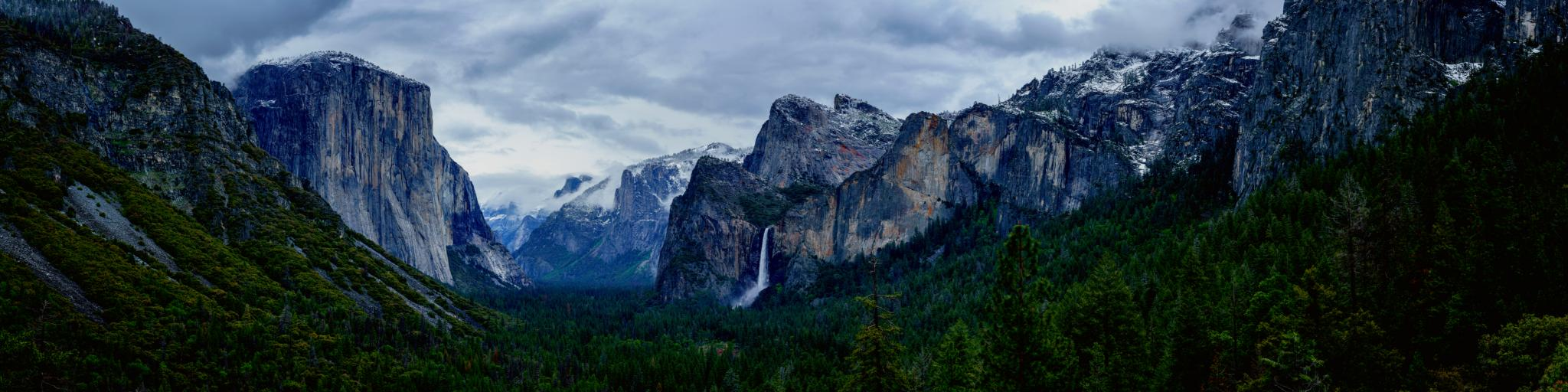 A breathtaking view of Rock formations, waterfall, and pine trees in Yosemite National Park on a gloomy afternoon