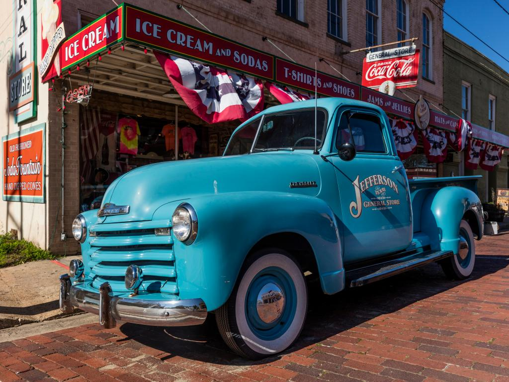 A blue classic chevy pickup outside the Jefferson General Store in Jefferson, Texas.