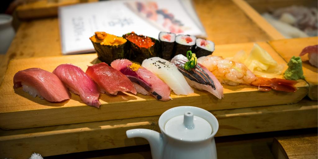 A wooden plank with a row of colourful sushi