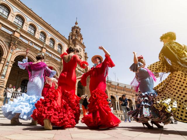 Flamenco dancers in Plaza España, Spain, two wearing red, the others in blue and pink dresses