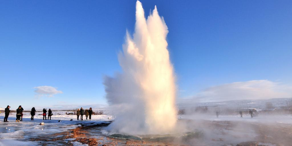 A geyser firing from the ground with people watching in Iceland