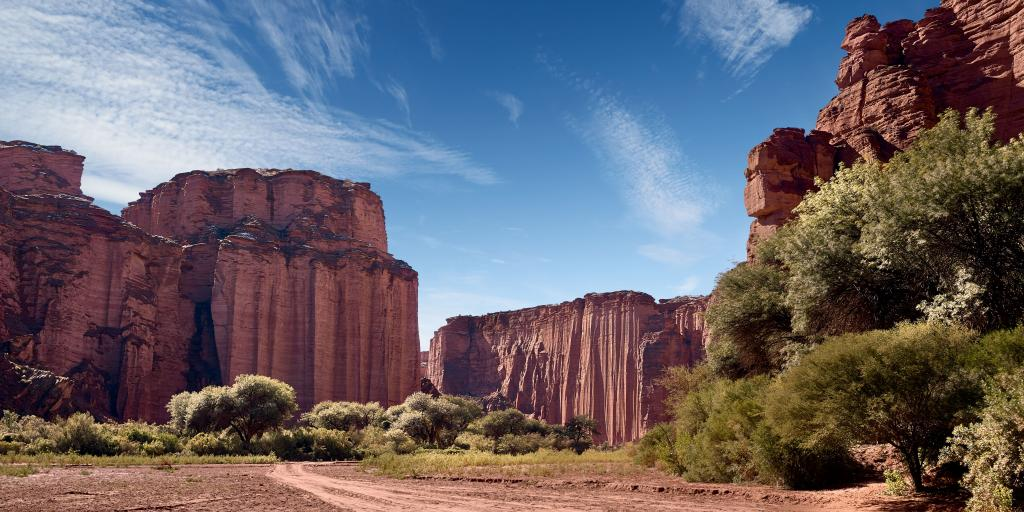 Steep red sandstone cliffs against the red desert in the Talampaya National Park, La Rioja, Argentina.
