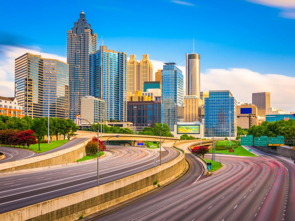 A long exposure shot of Interstate 85 with trees of red and green along the highway and the skyline of downtown Atlanta, Georgia in a sunny morning