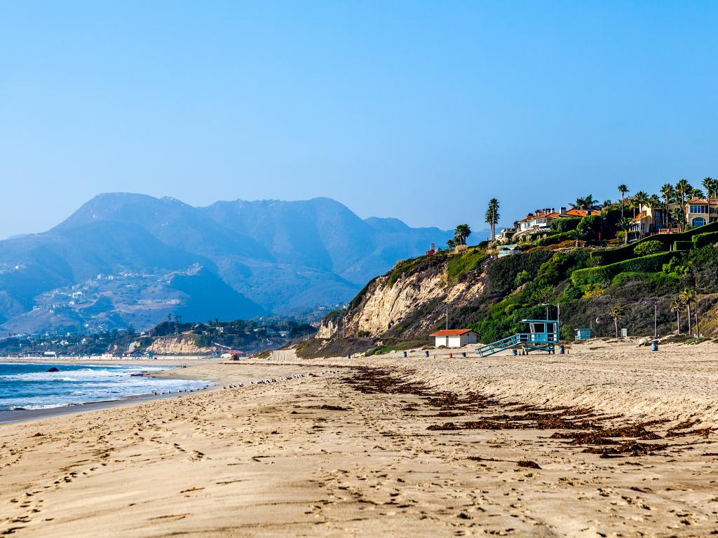 Malibu coastline with mountains in the background and mansions on a hill overlooking the beach.