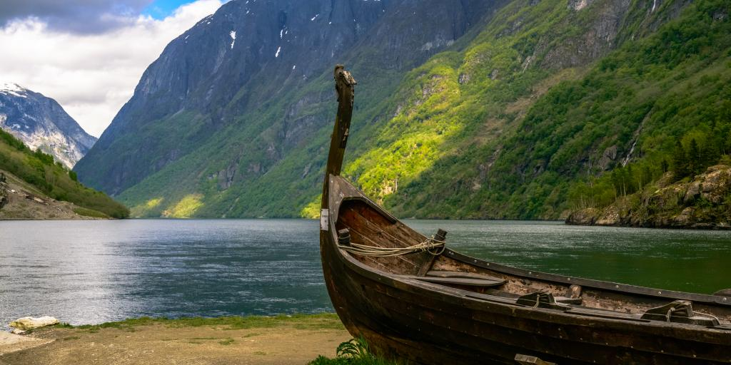 A boat sits on the banks of a fjord in Norway