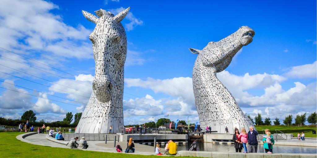 The giant horse heads of the Kelpies statue by Andy Scot tower over visitors to Helix Park on a sunny day in Falkirk, Scotland