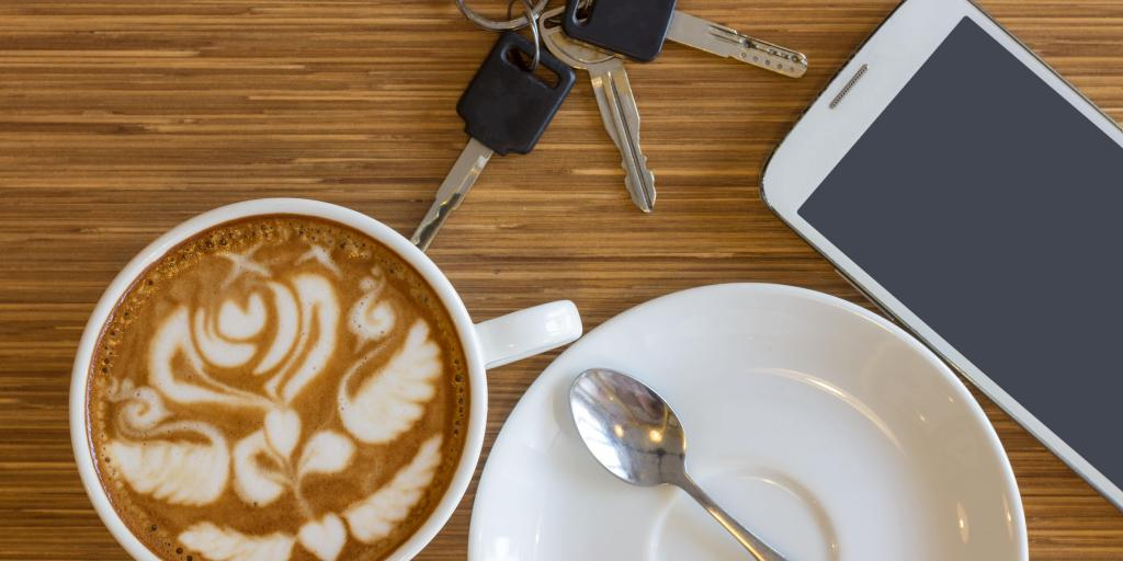 Coffee, keys and mobile phone on a brown surface