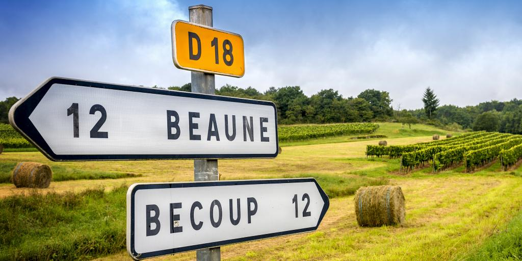 A French road sign pointing to Beaune in one direction and Becoup in another, with hay bales in the background