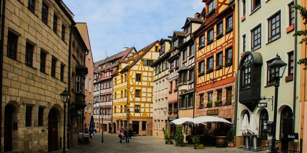 A view down Weißgerbergasse in Nuremberg with colourful timber framed houses either side and a cafe in the foreground