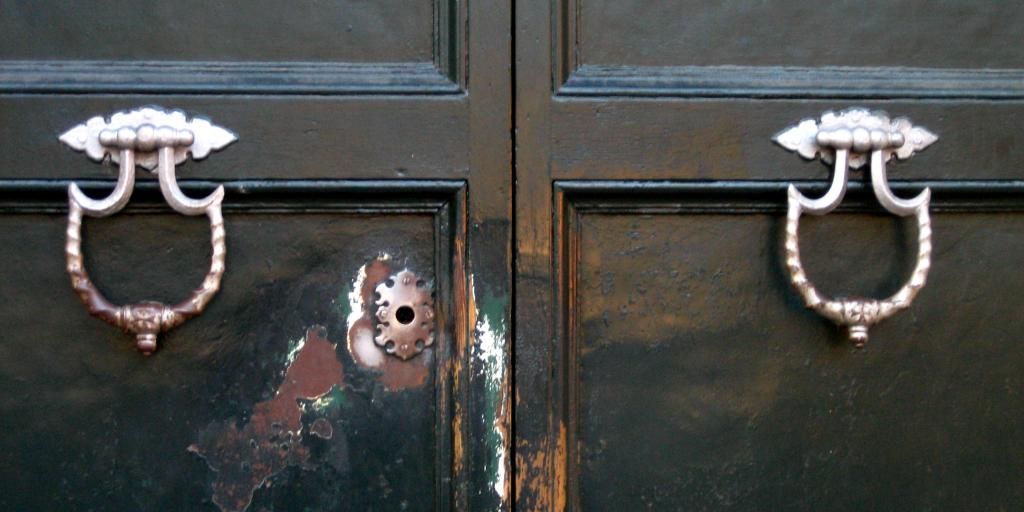 The Aventine Keyhole in Rome with scratched surroundings and two big brass knockers