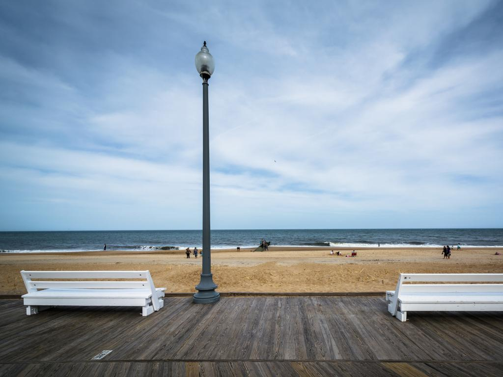 White benches on the boardwalk overlooking Rehoboth Beach in Delaware.