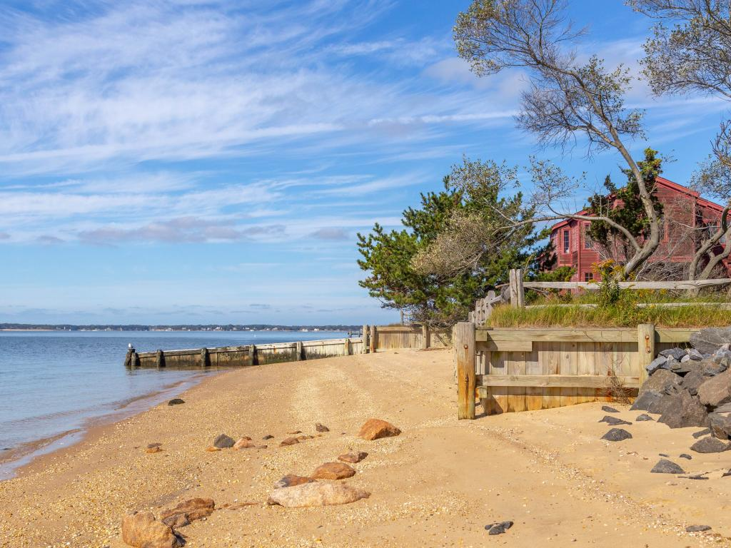A blue sky with thin sheets of clouds and calm seawater and a tree outside the red house by the beach and red rocks in the sand on a warm sunny day in Shelter Island, New York