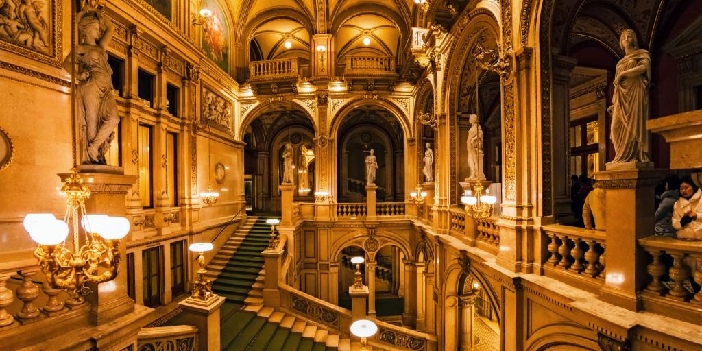 A curling staircase inside the Vienna State Opera House, Austria, with a green carpet and statues around the edges