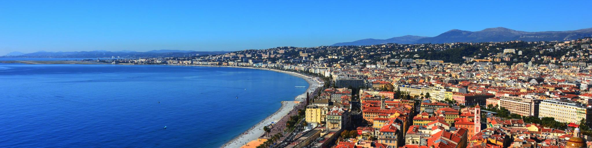 A view over the Promenade des Anglais in Nice, with the city's terracotta rooftops and the sea in shot