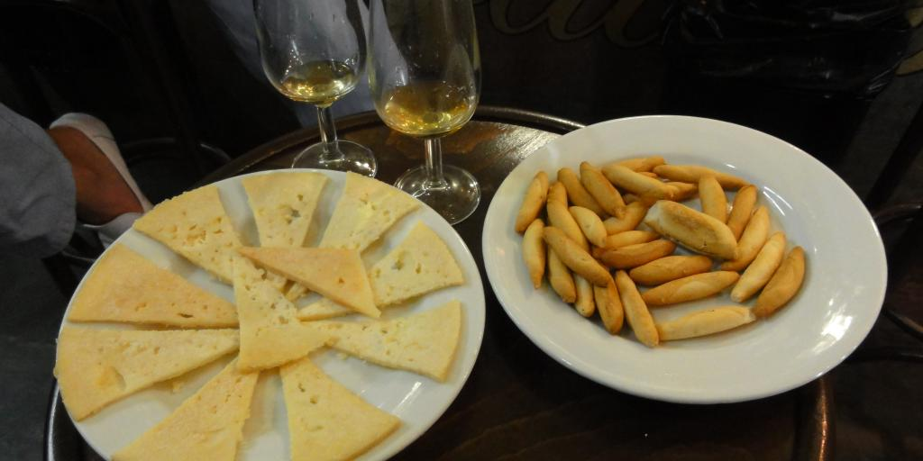 Slices of cheese and breadsticks and two wine glasses on a table at a tapas bar