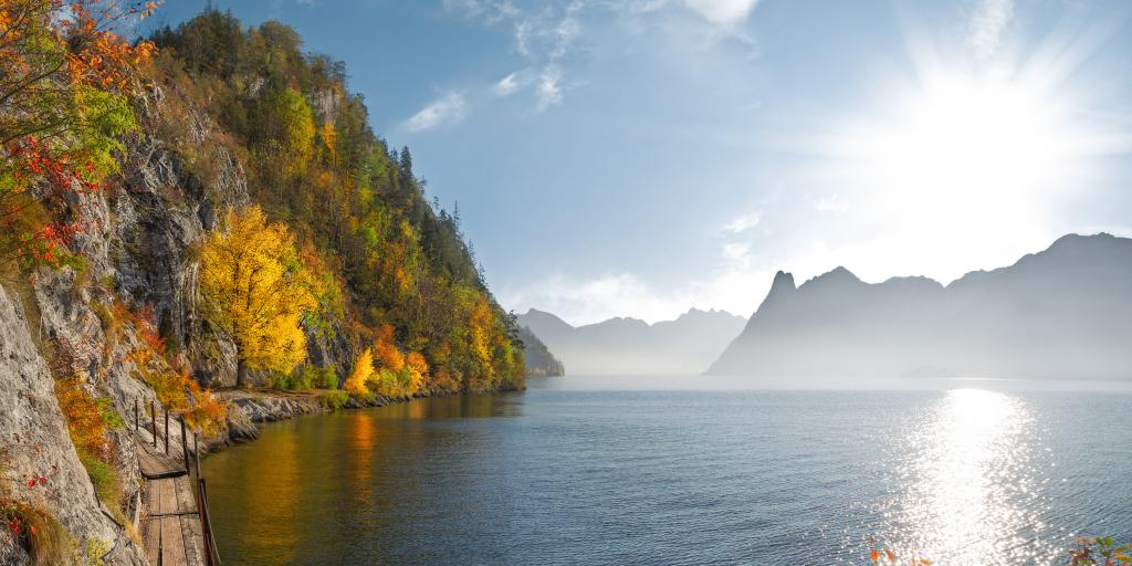 A walking trail next to a lake in Austria surrounded by colourful autumn leaves and a glittering lake