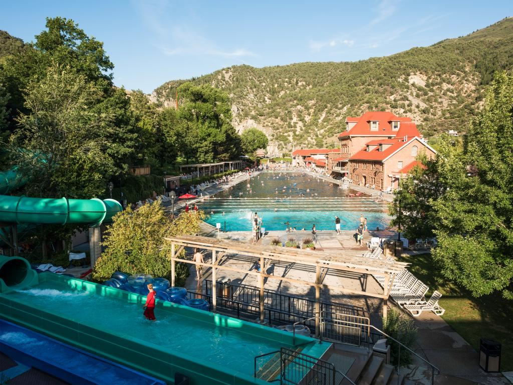 A wonderful sunny day at a public hot spring pool with water slide and a couple of people enjoying the hot water with a beautiful view of the mountain at Glenwood Springs, CA