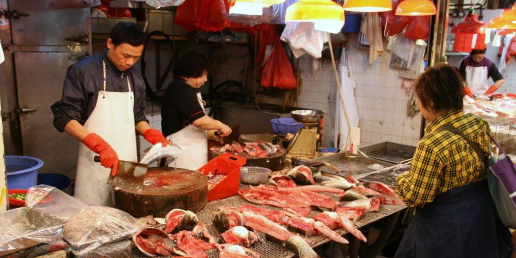 A man gutting a fish at a fish stall in a Hong Kong street market, with a woman cooking fish in the background