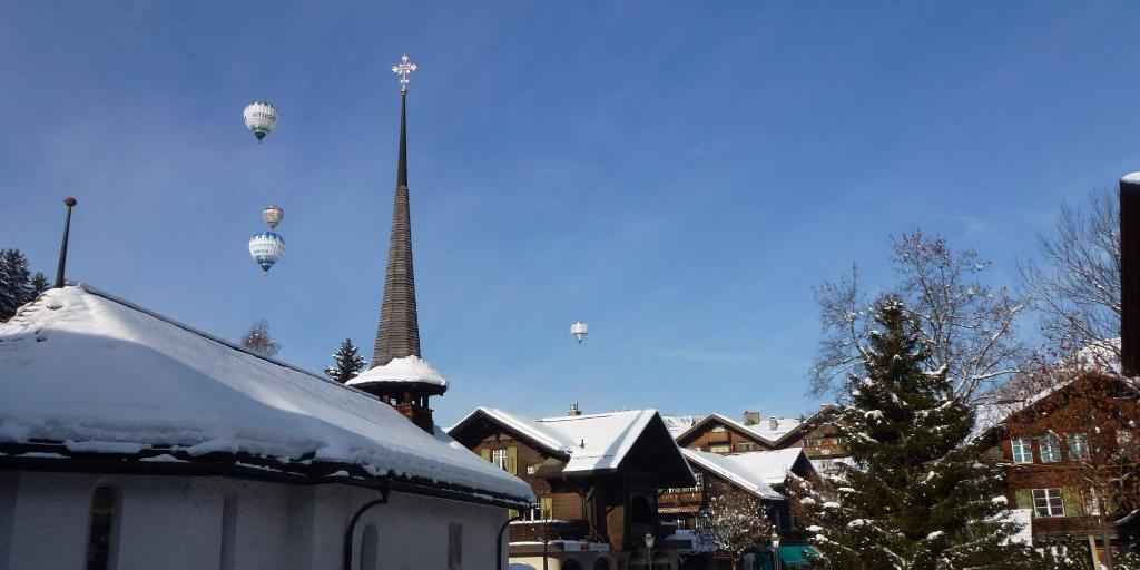 Hot air balloons taking off over the town of Gstaad, Switzerland, with a church spire in the foreground