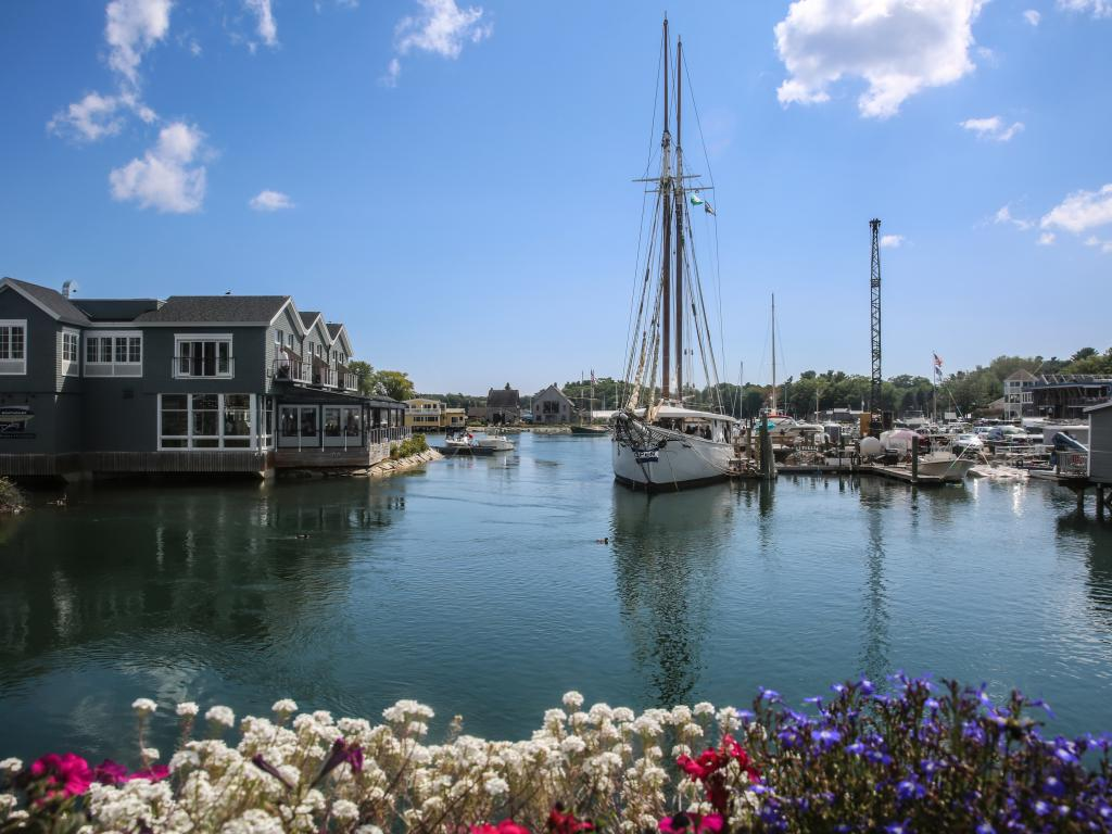 Boats in a quiet harbor with pretty houses in Kennebunkport, Maine.