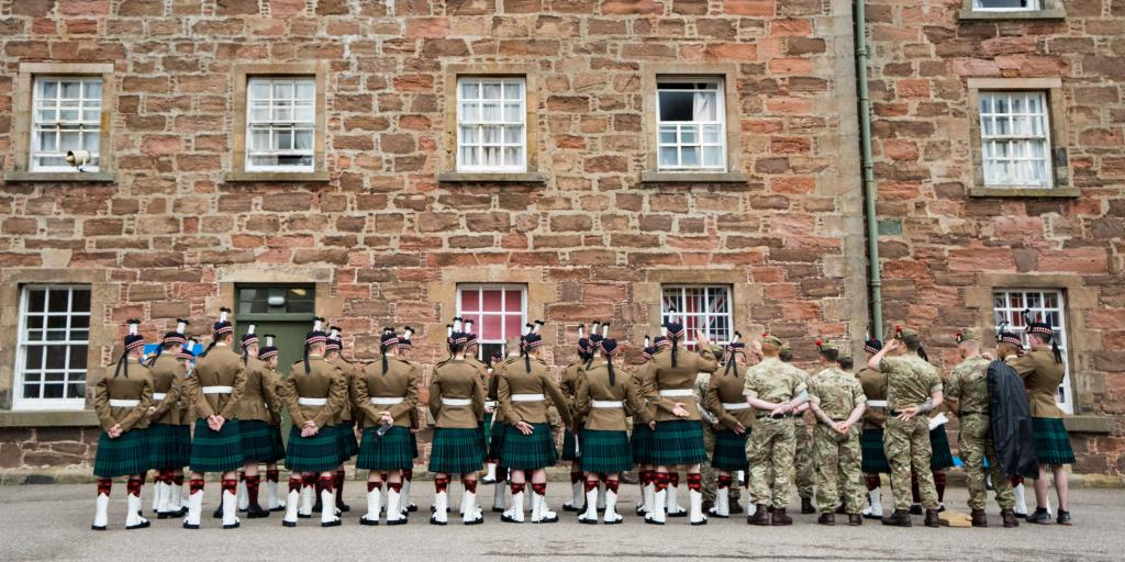 Soldiers wearing kilts and army fatigues with their backs to the camera outside a stone barracks building at Fort George, Scotland