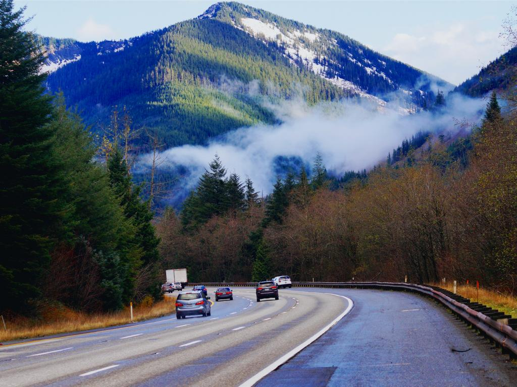 Early morning with cars driving along Snoqualmie Pass road passing tall green pine trees and taking in the breathtaking view of the mountain with a thin sheet of fog