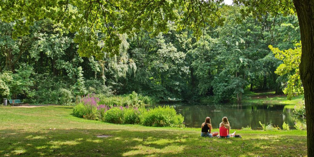 Two women sit on the grass and look out at a pond inside the lush green Tiergarten park in Berlin