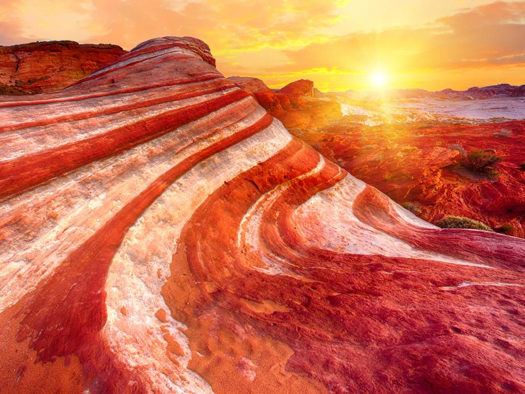 The orange-red sunset illuminating the Fire Wave Rock in Valley of Fire State Park, Nevada