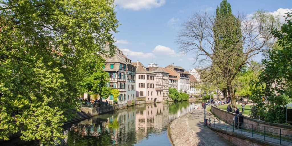 A river lined with half-timbered houses and lush green trees in Strasbourg's Petit France neighbourhood