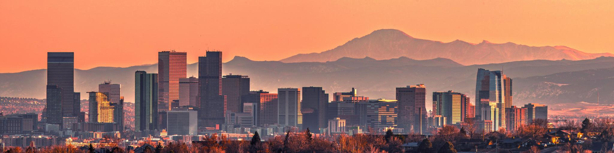 Denver skyline at sunset with Rocky Mountains in the background.