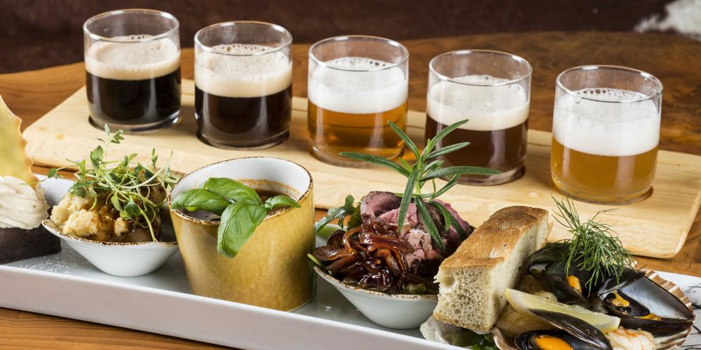 Glasses of beer paired with a variety of meat and vegetarian dishes at Ægir BrewPub