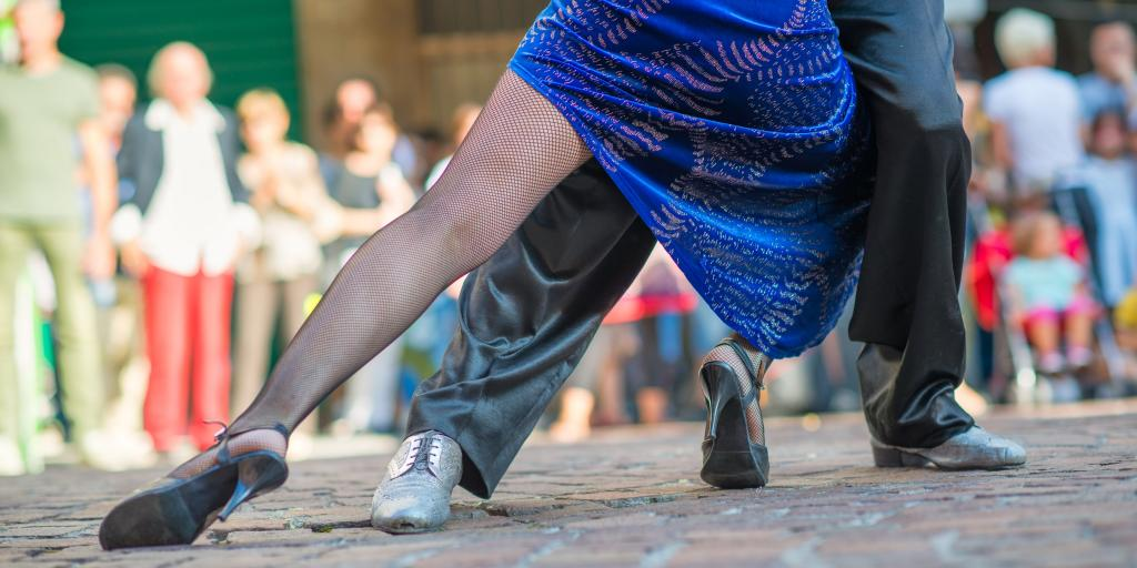 Feet and legs of a couple dancing tango in the street among the people in Buenos Aires, Argentina